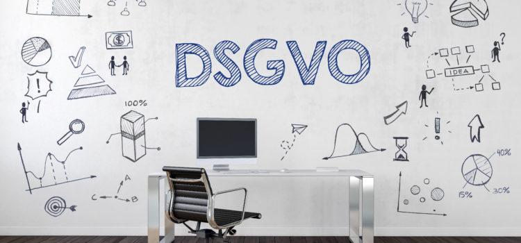 Am Bild ist ein Büroschreibtisch vor einer bemalten Wand zu sehen. Die Bemalung der Wand zeigt Elemente der Datenschutzgrundverordnung (kurz DSGVO)