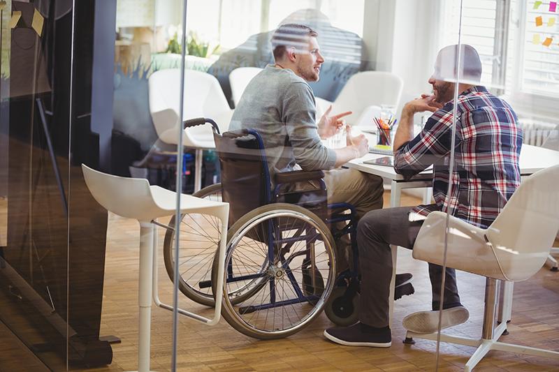 Am Bild sind zwei Männer - einer davon mobilitätseingeschränkt und in einem Rollstuhl sitzend - in einem Besprechungszimmer zu sehen.