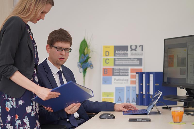 Das Bild zeigt Bettina Eder und Mathias Past. Bettina Eder überreicht Mathias Past – an seinem Büroschreibtisch sitzend - einen Projektordner.