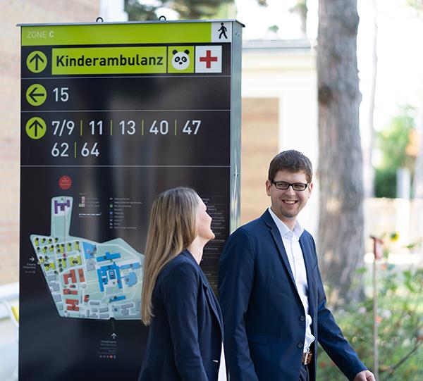 Am Bild sind Bettina Eder und Mathias Past zu sehen. Sie befinden sich vor einem von Logsol konzipierten Leuchtschild am Areal des Wilhelminen Spitals.