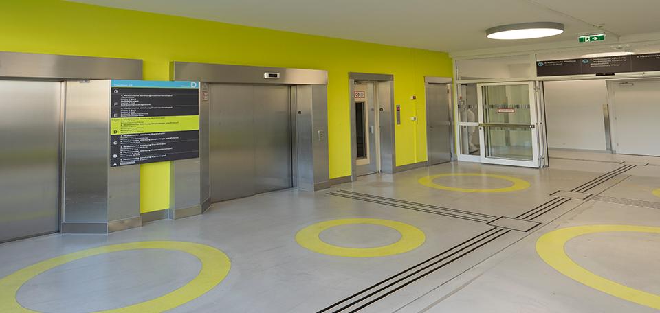 Das Bild zeigt einen Innenraum des Wilhelminenspitals. Taktile Leitsystemlinien führen durch den Innenraum zur Ruftaste eines Aufzuges. Zwischen den Aufzugsportalen ist ein visuelles Leitsystemschild angebracht.