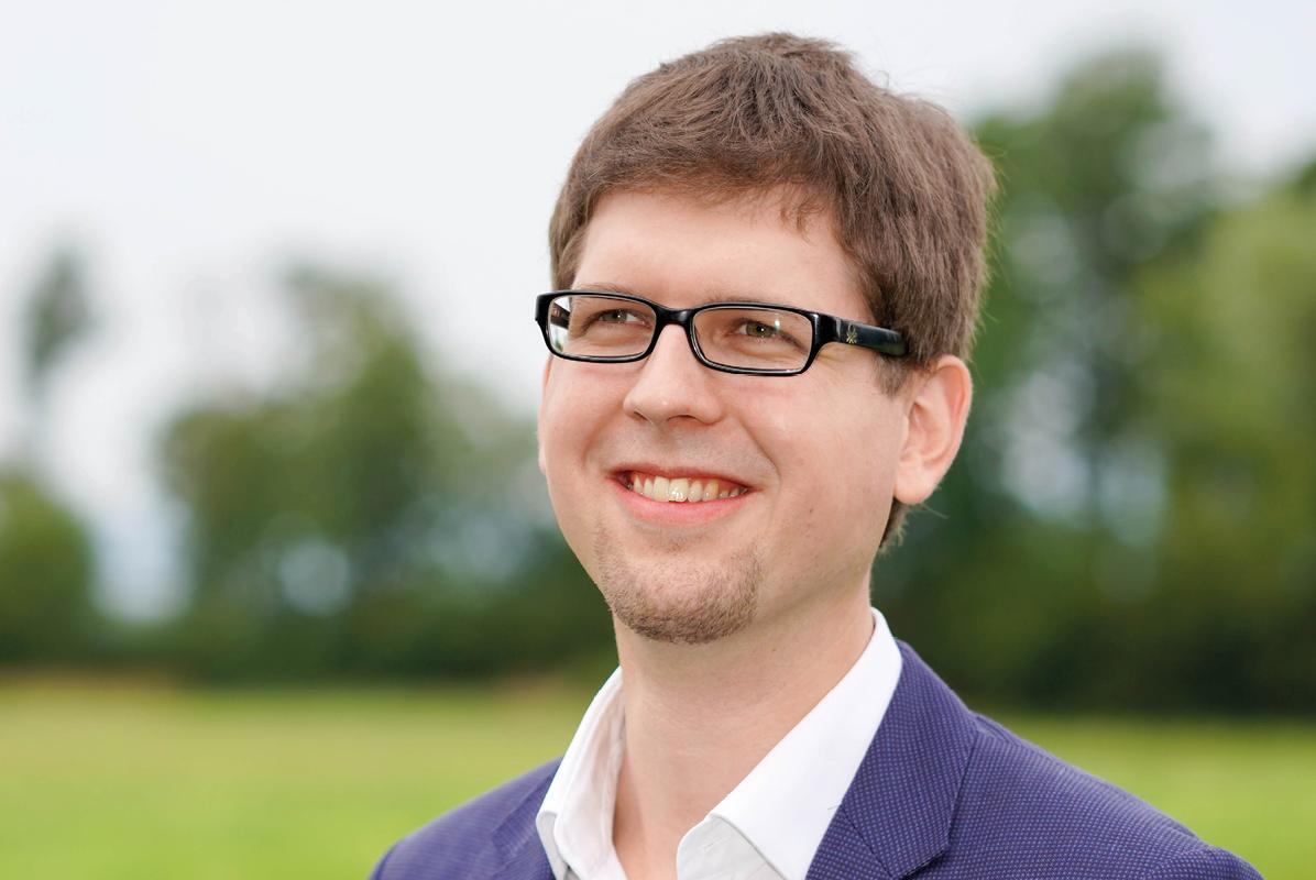 Portraitfoto von Mathias Past. Im Hintergrund eine Gras- und Waldlandschaft