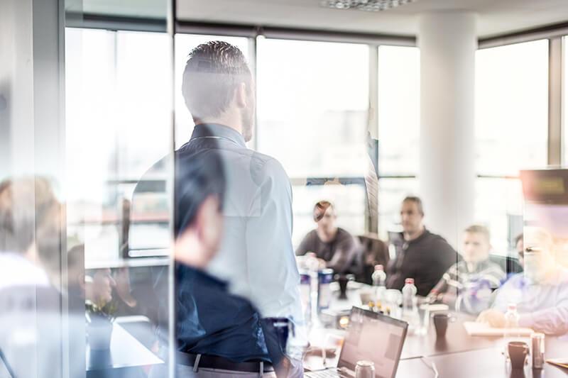 Am Bild sind mehrere Personen in einem Besprechungszimmer zu sehen. Ein Mann steht, während die restlichen Personen sitzend am Besprechungstisch sitzen und diesen ansehen.