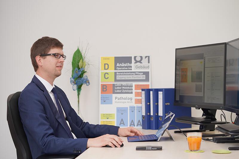 Das Bild zeigt Mathias Past sitzend vor seinem Büroschreibtisch. Auf seinen Bildschirm sind Projektarbeiten zum Wilhelminen Spital geöffnet.