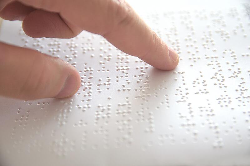 Das Bild zeigt den Finger einer Person, welche die Braille Schrift liest.
