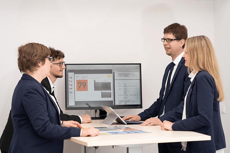 Das Bild zeigt das Logsol-Team während einer Besprechung. Am Schreibtisch befindet sich Bildschirm, welcher Projektinhalte des zu besprechenden Projektes darstellt. Links: Andreas Stefl und Karin Annerl. Rechts: Mathias Past und Bettina Eder