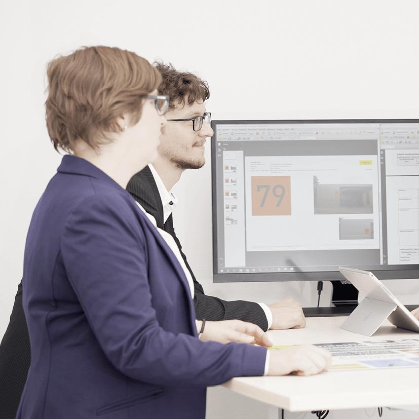 Am Bild sind Andreas Stefl und Karin Annerl an einem Schreibtisch während eines Meetings zu sehen.