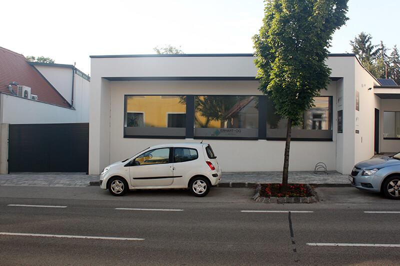 Am Bild ist das weiße Bürogebäude von Logsol von der Frontansicht zu sehen. Vor dem Bürogebäude befinden sich parkende Autos und ein Baum.